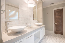 White modern bathroom with dual sinks and marble elements