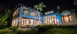 Exterior night time shot of Coastal Dutch home built buy Perrone Construction