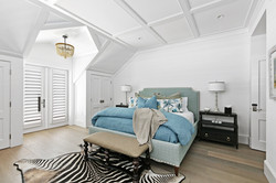 Peaceful coastal inspired bedroom with high ceilings
