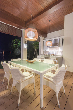 Outdoor living space with seating and kitchen lit up in the evening