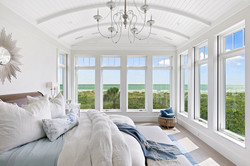 Waterfront view bedroom with tall windows and chandelier