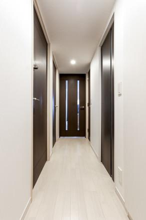ブラウン調の建具が引き立つ、段差のないバリアフリー廊下に。|リフォームの施工事例|廊下