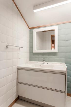 2階の洗面化粧台も収納たっぷり。エコカラットで清潔感あふれるインテリアを演出! リフォームの施工事例 洗面化粧台
