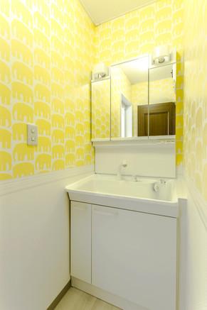 明るいイエローの内装でコンパクトな洗面所の圧迫感を解消! リフォームの施工事例 洗面化粧台