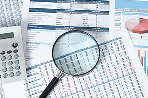 financial documents with magnifying glas