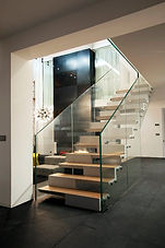 An interior staircase with glass frame and balustrades