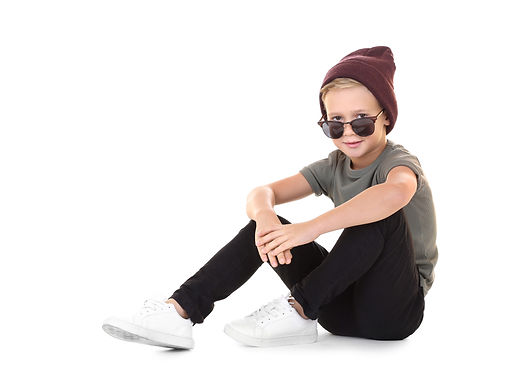 Cute fashionable boy sitting on white ba