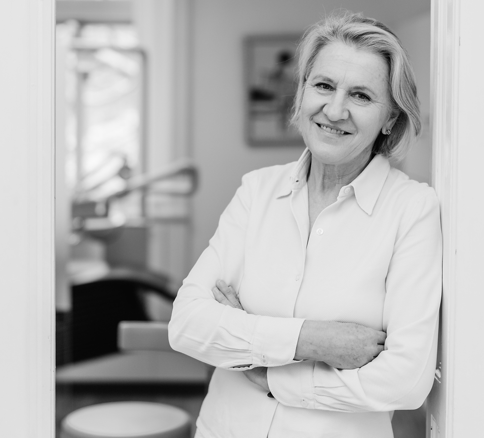 Black and white portrait of the female middle-aged blond dentist, Dr. Elfriede Weber. She leans cross-armed against a white door frame, wearing a white blouse, smiling at the camera. Behind her the dentist office.