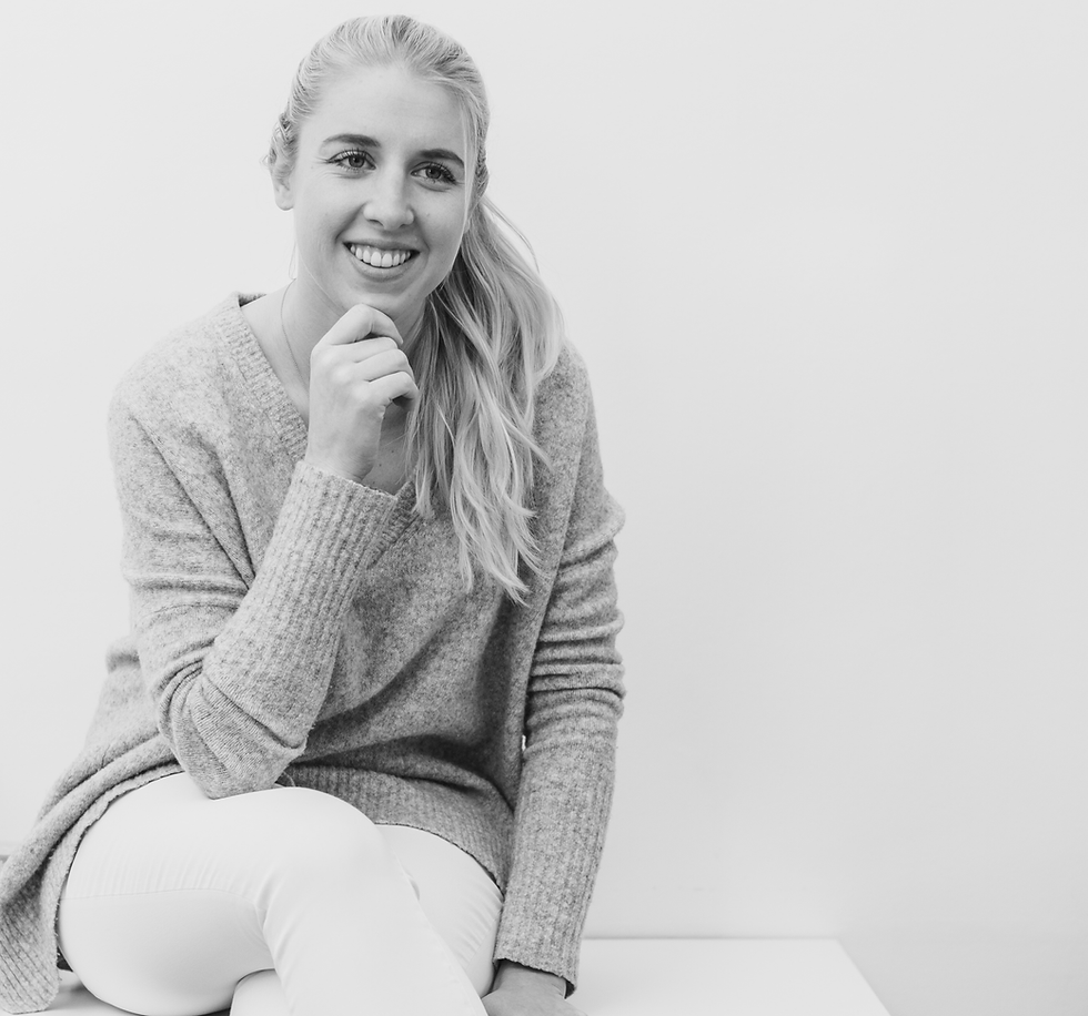 Black and white portrait of the young female blond dentist, Dr. Stefanie Weber. She wears a wool sweater and white jeans and she sits on a white surface. Holding her chin with her right hand, smiling.