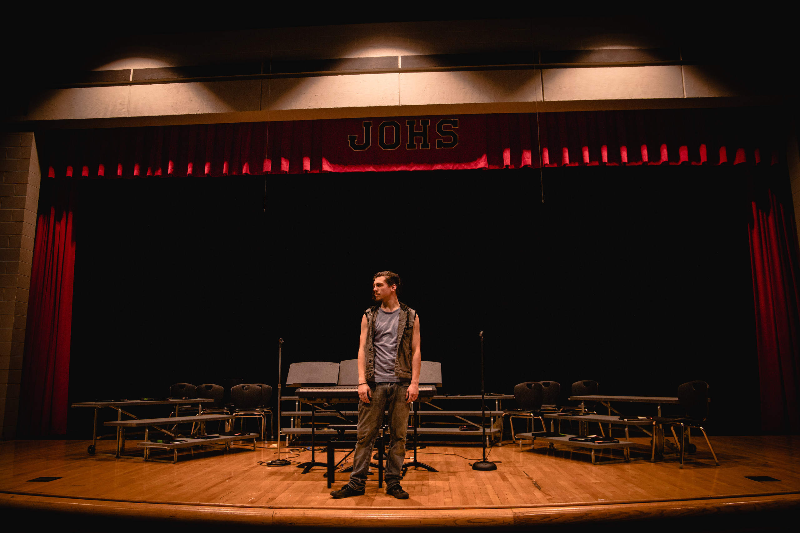 A high school senior boy poses on an empty theater stage.