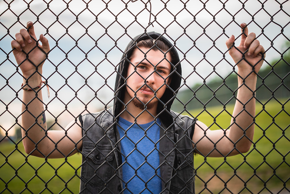 A Senior Boy in a dark hoodie stands behind a chain length fence.