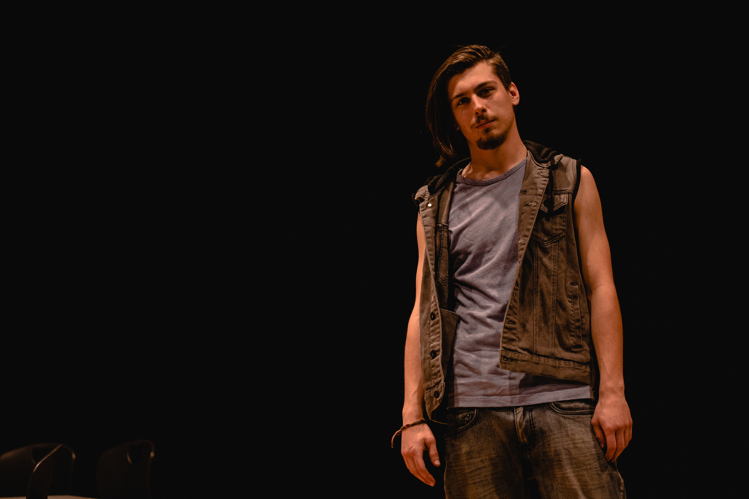 A high school senior boy stares directly into the camera on a dark, dramatically lit theater stage.