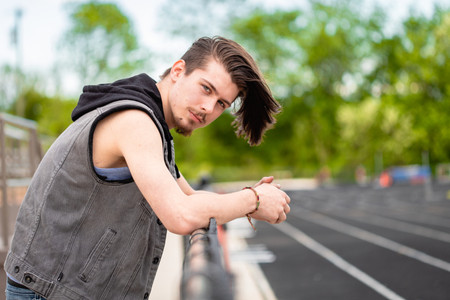 Senior boy leans arms on a chain length fence at a high school football field, between the bleachers and the track.