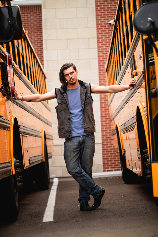 A senior boy dramatic poses between two bright yellow school buses at his high school campus with one hand on each bus.