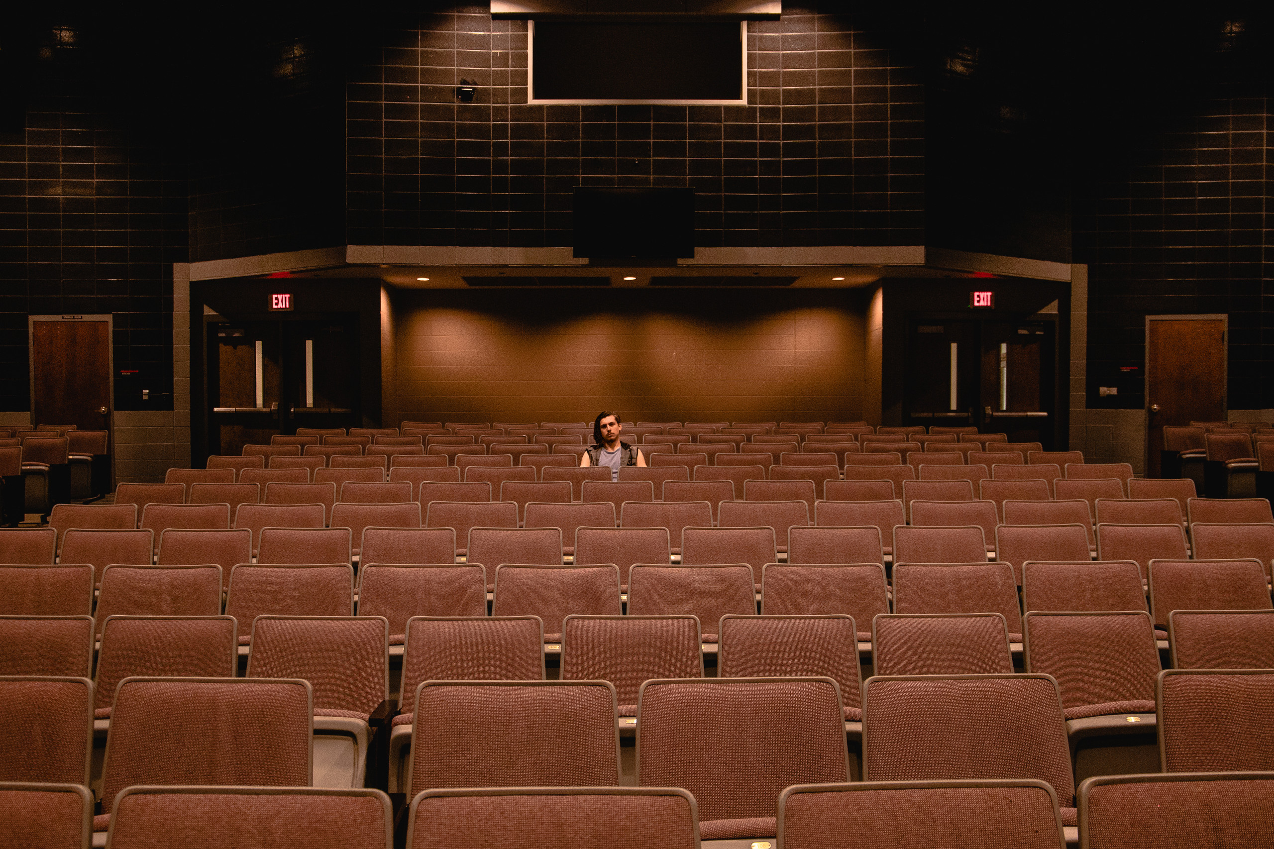 A high school senior boy sits in the middle of an empty theater.
