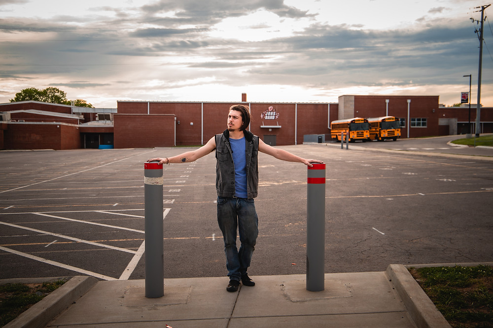 A senior boy poses between two posts in the parking lot of John Overton High School in Nashville Tennessee while dramatic clouds roll in.