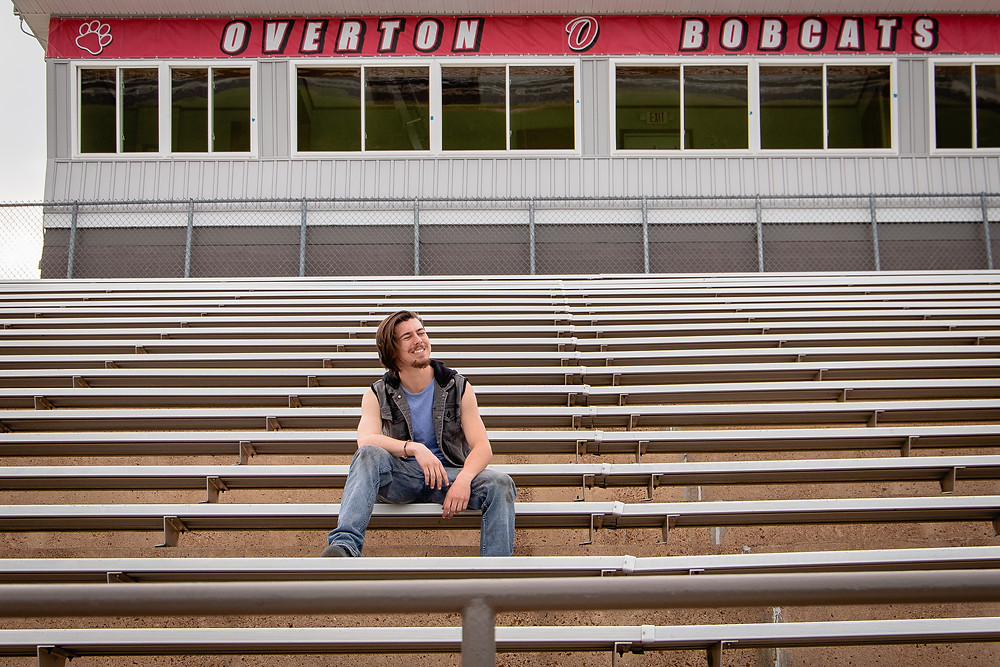 A senior boy at John Overton High School in Nashville Tennessee laugh to himself on the metal bleachers of the football field.