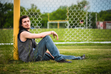 Senior boy with long hair leans against a football goalpost with a vibrant green grass and soccer net background.