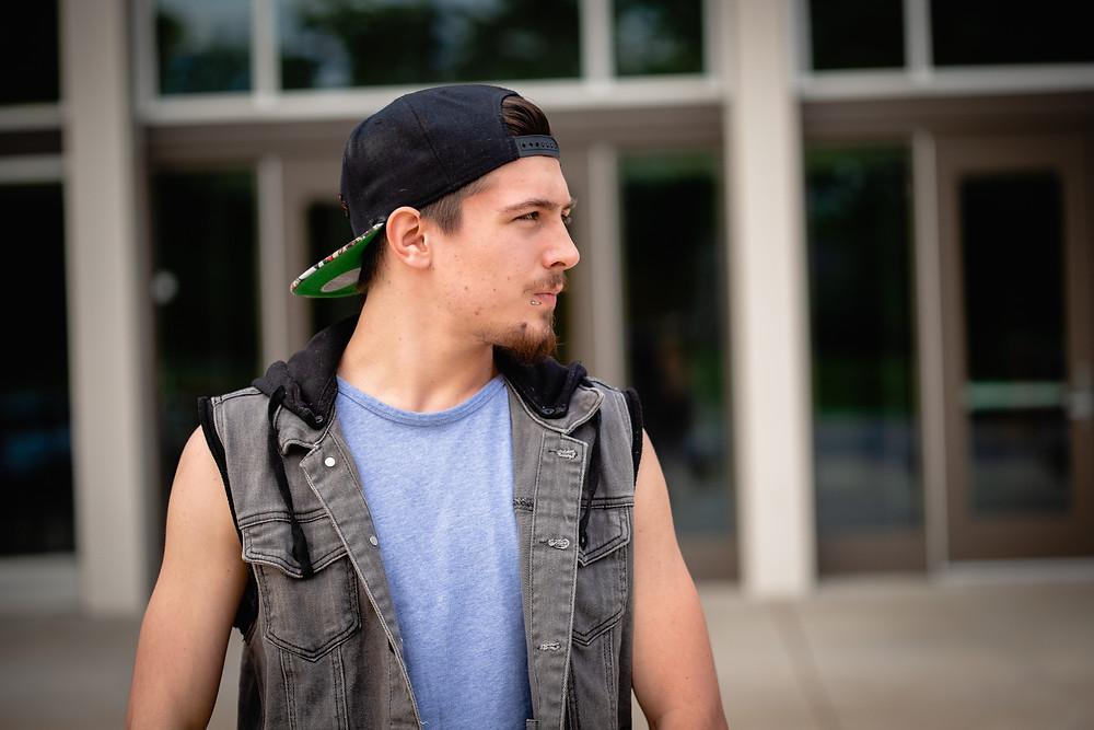 A senior boy in a backwards baseball cap stares off at a 90 degree angle to the camera.