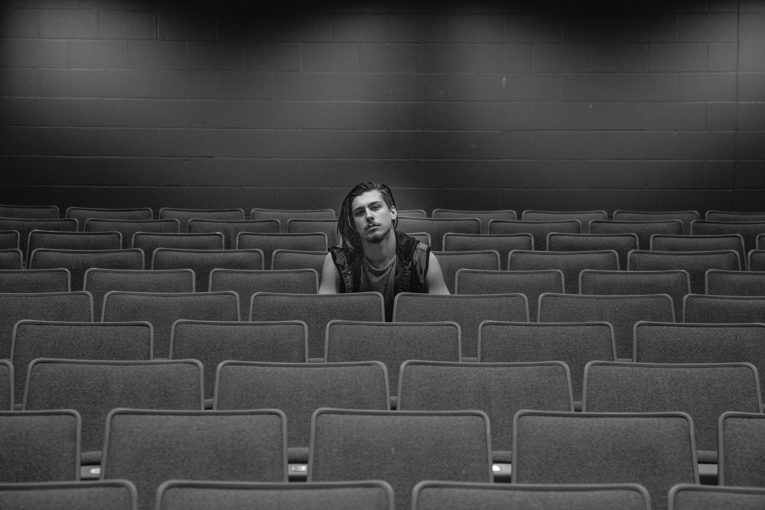 Black and white image. A high school senior boy sits in the middle of an empty theater.