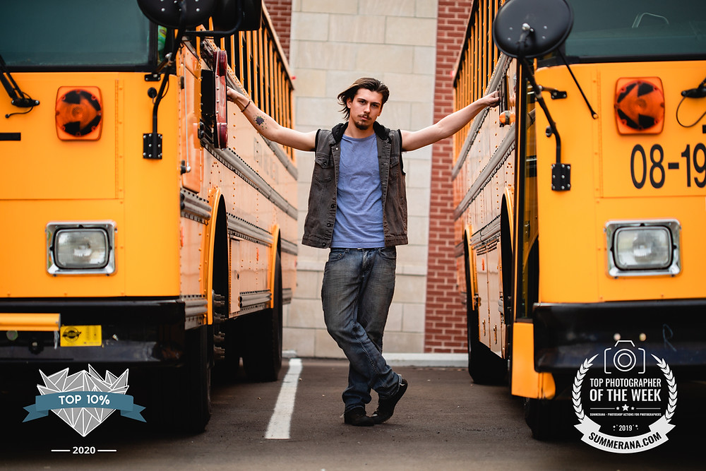 A class of 2018 senior boy poses with one hand on each of two bright yellow John Overton High School buses in Nashville Tennessee.