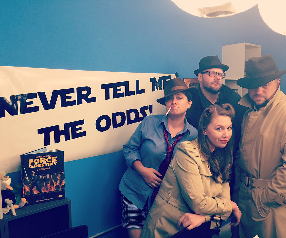 A very Noir team of players, donned in fadoras and trench coats, stand ready for action in front of a Never Tell Me The Odds banner at the Saving Throw Show studio.