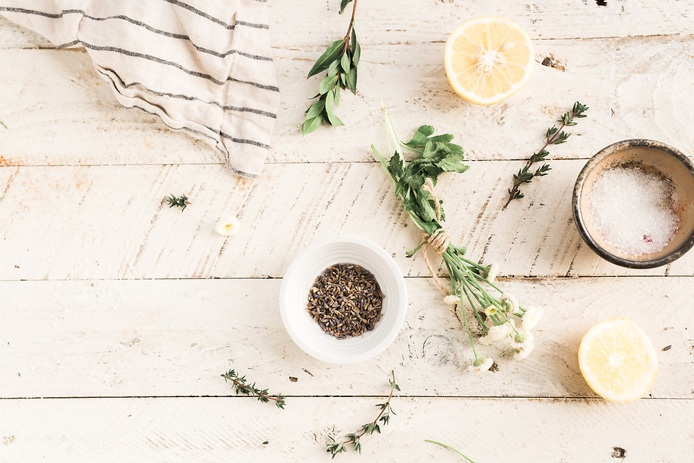 Bowls of salt and pepper and herbs and lemon on wooden kitchen table.