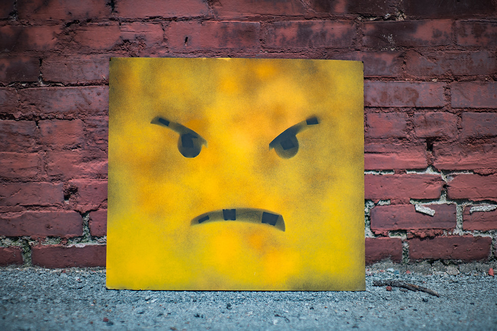 Angry, unhappy and unhealthy yellow square with a scowling face, stacked up against a brick wall