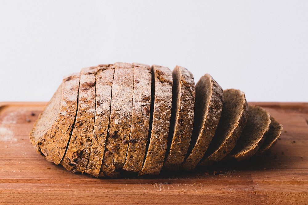 Homemade sliced loaf of brown bread on a wooden chopping board