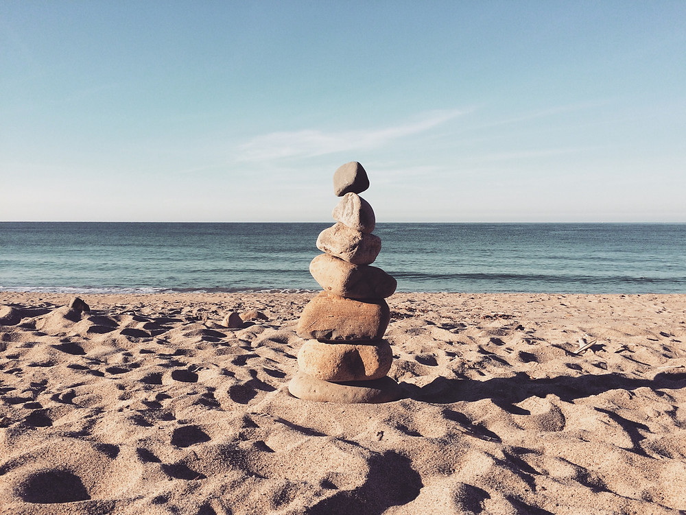 Rocks balanced on top of each other on a sandy beach