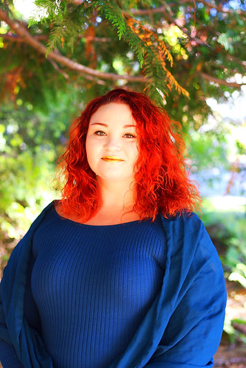 Andrea Oakunsheyld is standing and smiling in front of a green forest background. Andrea is a white, curvy, femme with curly red hair worn down. She is seen from the waist up wearing a deep blue sweater dress and matching blue silk shawl. She is wearing eye makeup and gold lipstick.
