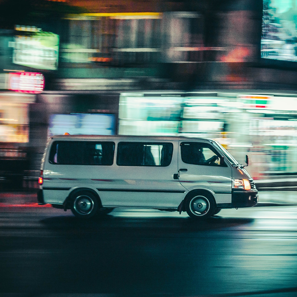A white van speeds along a road at night.