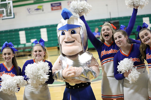 SCA High School cheerleaders posing with Warrior mascot