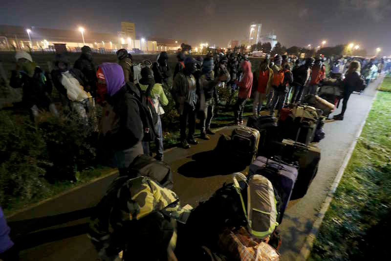 Migrants with their belongings queue as their evacuation and transfer to reception centres in France, and the dismantlement of the camp called the 'Jungle' in Calais, France, starts October 24, 2016. — Reuters pic