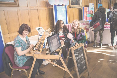 lyn elrick during a coprorate event at aberdeen university drawing digital cartoons at her easel