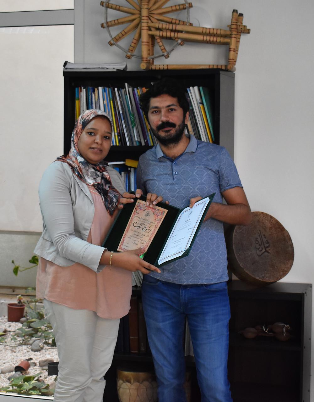 Arabic student receiving a certificate