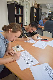 Students writing Arabic calligraphy