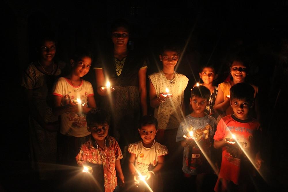 Children at Prema Vasam light earthen lamps