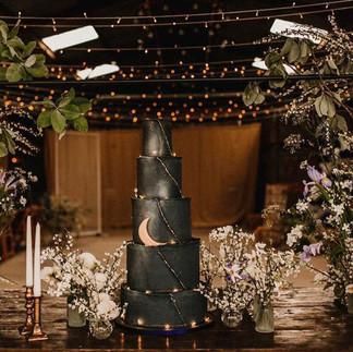 Silver Beam foliage with broom, tulips and ranunclus cake table  Venue: Grange Barns Photographer: Carla Blain Cake:  The Red Rose Cake Company