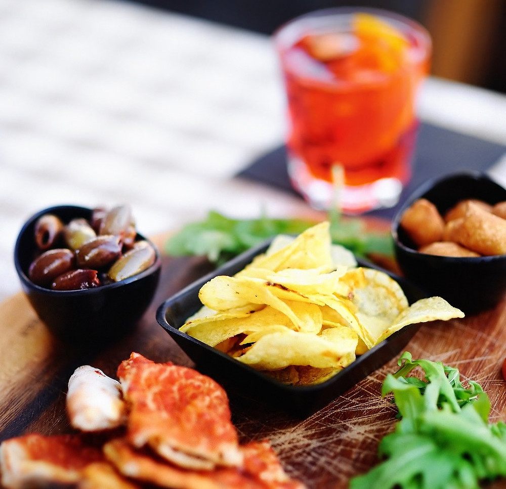 Things like chips, olives, salumi, and small sandwiches are often seen at aperitivos.