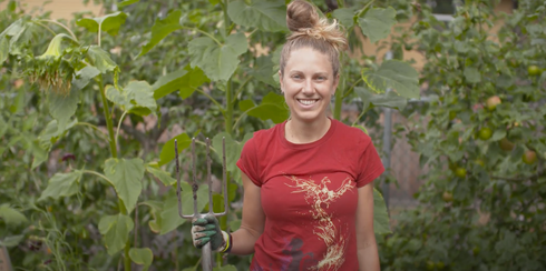 Woman stands with garden pitch fork infront of garden crops