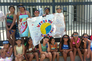 """Please donate to Project 2020 water polo team. Mavericks hold """"Thank You"""" banner before practice at pool side"""