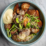 Uppopaistettuja perunoita kulhossa, lisukkeena parmesani ja aioli