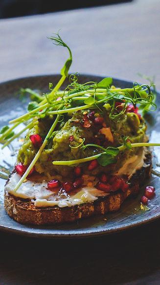 Green Hippo tunnettu avokadoleipä. Spelttileipä lautasella, leivän päällä avokadotahnaa, herneenversoja ja granaattiomenaa.
