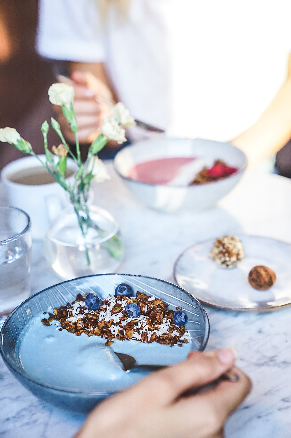 Blue Smoothie bowl with homemade granola in the foreground opposite a red smoothie bowl in a white bowl.