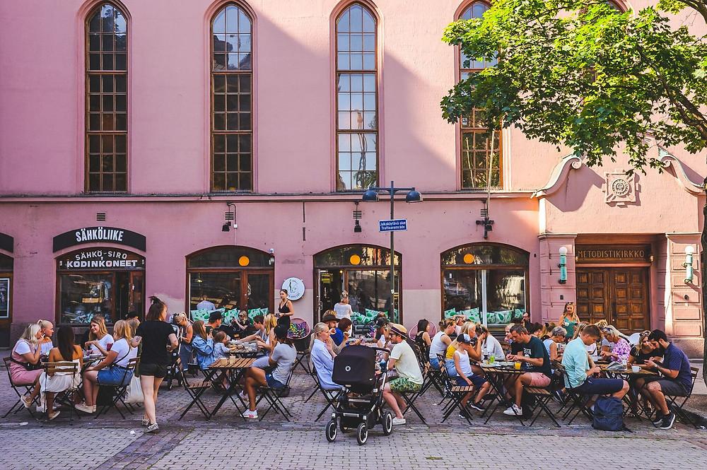 Green Hippon kesäterassi. Terassi on täynnä ihmisiä aurinkoisena päivänä, tarjoilija tuo ruokaa pöytään.
