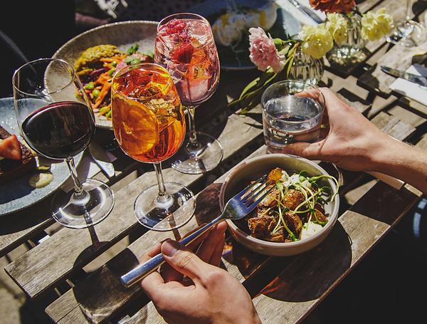 Paistettuja perunoita kulhossa, vesilasi, aperol spritz, pink gin&tonic ja punaviinilasi