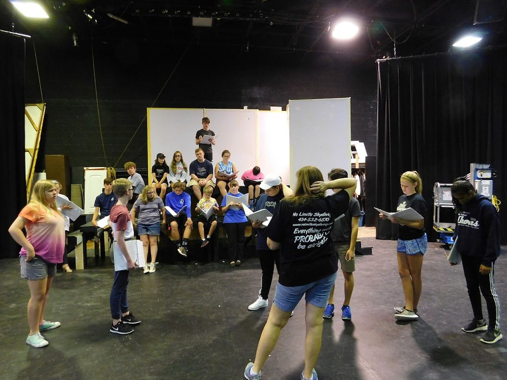 A blackbox rehearsal of Damn Yankees. Kids are all over the platforms while a camp counselor supervises