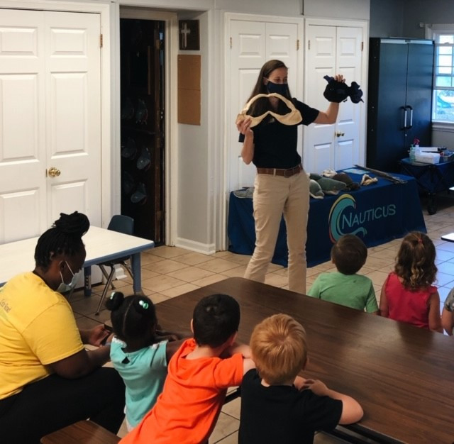 A woman teaches a group of children at Nauticus.