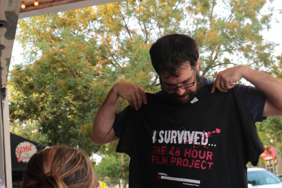 """A filmmaker holds a shirt up to themselves- it reads """"I survived the 48 hour film festival"""""""